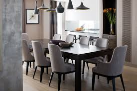 tom dixon pendant lighting over large table and gray grey upholstered dining chairs