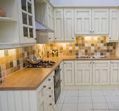 wooden laminate counter using mosaic backsplash and elegant white cabinet paint for square shaped kitchen layout