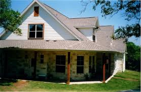 texas style home with partial wrap around porch by texas home builder