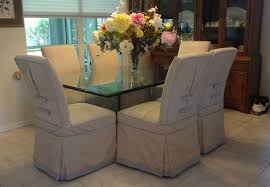 six dining room chairs slipcovered with a moire fabric and trimmed with tabs and ons