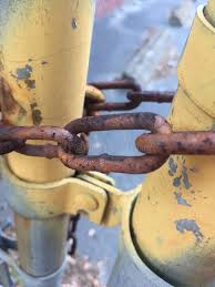 chain link fence poles locked rusty rust grunge yellow ling paint metal stock image