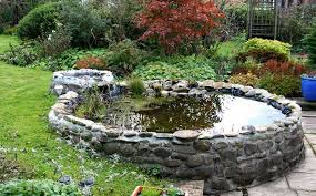 bridging the edge of a stone patio and the lawn this raised garden pond is framed in a low concrete stone wall with a small upper level reservoir feeding