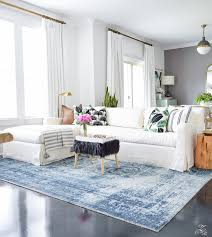 zdesign at home summer home tour blue vintage inspired rug white slip covered couch white walls
