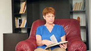 old lady sitting in a leather wing chair reading a book 4k slow
