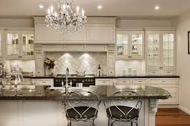 modern traditional kitchen design with white stone backsplash and black granite countertop kitchen island under crystal chandelier