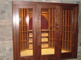 a vigilant full glass door with sidelights provide both viewing and access to a homes small mahogany wine cellars traditional wine cellar