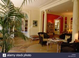 wooden parquet floor and black wicker armchairs in livingroom with large houseplant and classical pillars