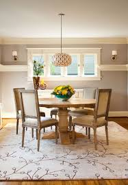 gorgeous dining room with round wood table and rustic chairs on white fl pattern rug area