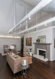 whitetongue and groove vaulted ceiling with exposed beams this track lighting but pointed up to create a glow ceiling track lighting