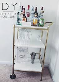 white wooden and metal bar carts ikea with liqoours and wine glasses and  gray straw plus