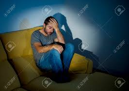 young sick man sitting on couch at home scary and desperate stock photo young sick man sitting on couch at home scary and desperate suffering insomnia depression nightmares emotional crisis mental disorder