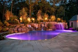 fabulous lighting design house. fabulous backyard lighting option with curved pool and brick deck around lush vegetation also stone placement small waterfall in purple landscape design house