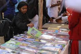a girl flips through a book at one of the many stalls in bhima koregaon scores of s anti caste literature in pocket sized books often in marathi