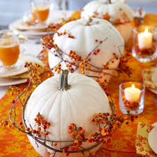 White pumpkins encircled by bittersweet vine and surrounded by candles make  a perfect arrangement on an