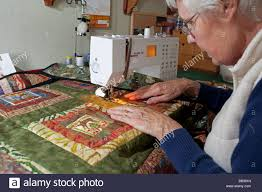 Woman sewing patchwork quilt using Bernina sewing machine at home ... & Woman sewing patchwork quilt using Bernina sewing machine at home UK Adamdwight.com