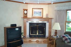 wood corner fireplace with tile and picture above