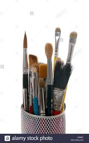 paintbrushes in a metal mesh holder on white background