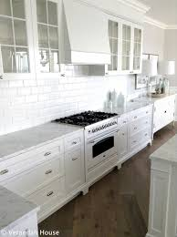 gorgeous kitchen with white cabinetry brushed nickel hardware carrara marble countertops and a beveled subway tile backsplash