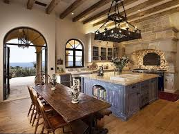 Mediterranean style kitchen with exposed brick archway and rustic dining  island