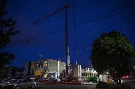 floodlights illuminate the job site at harvard flats on east thomas street on capitol hill