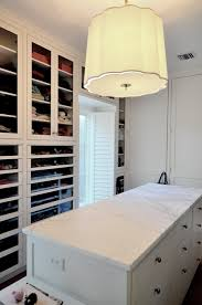amazing walk in closet design with glass front built in cabinets white closet island with marble countertop and barbara barry simple scallop pendant