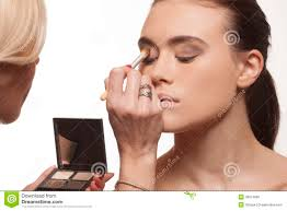 beautician applying eye makeup
