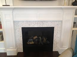 white and light grey small tile glass mosaic fireplace surround with victorian style white fireplace mantel and some ornaments dark brown teak hardwood