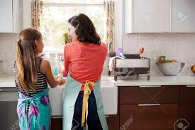 Mum And Daughter Washing Hands At Kitchen Sink Back View Stock