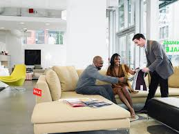 salesclerk showing fabric samples to man and woman in furniture store 001 5995a043c acdbf