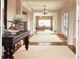 unusual chandelier or large patterned rug also black console table with greenery for hallway decorating idea