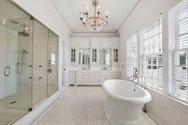 luxury bathroom design with clawfoot tub and crystal chandelier using small ceramic tile flooring