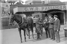 horse drawn cab and motor taxi stand side by side outside the subway prior to the