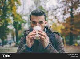 Download this free photo about young handsome man drinking coffee outside and using phone, and discover more than 7 million professional stock photos on freepik. Young Man Drink Image Photo Free Trial Bigstock