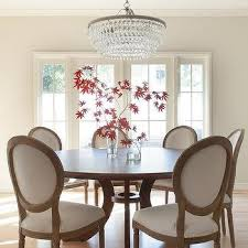 round dining table with vintage french round fabric side chairs