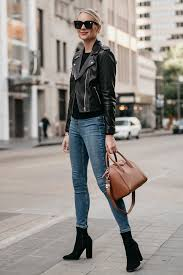blonde woman wearing black leather jacket denim skinny jeans black booties givencny antigona cognac satchel fashion