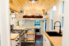 an interior shot of a kitchen and sleeping loft custom ordered tiny homes