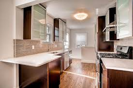 small contemporary galley kitchen with brown cabinets with frosted glass doors and white quartz counters