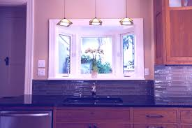 kitchen sink light three beautiful pendant lamps over the kitchen black sink plus its gold tone faucet a small kitchen window garden with a beautiful green