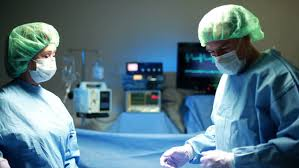 surgeon nurse stock video clip of two surgeons performing surgery are assisted by