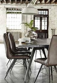 beautiful dining room setup with concrete floors leather chairs brick walls exposed wooden