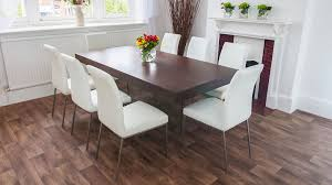 rectangular wooden dining table and white dining chairs