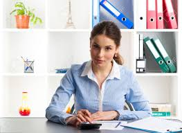 young female credit consultant calculating interest rate sitting at desk in the office smart woman