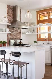white kitchen with brick accent wall