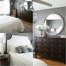 dark wood for furniture. benjamin moore amherst gray and kendall charcoal are the best dark paint colours shown here in bedroom with wood flooring furniture for