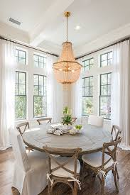 chic cote dining room features a gold beaded chandelier hanging over a round salvaged wood dining table lined with french cafe chairs and white slipper