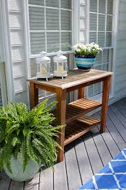 Potted plants and flowers on a teak potting table to decorate a backyard  deck in a
