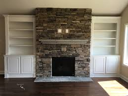 stacked stone fireplace with a flagstone mantle and custom built in bookcases