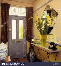 front door tableTelephone and flowers on hall table with curtains at the front
