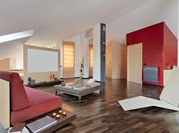 A beautiful open concept living room with multi-tonal wood floors and a  rich red