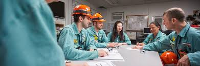 employees in coveralls reviewing doents in meeting around a table